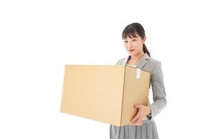 荷物を運ぶ若いビジネスウーマンの写真素材 [FYI04720511]