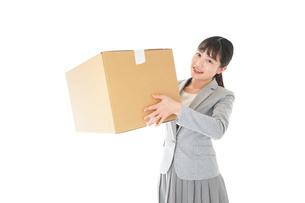 荷物を運ぶ若いビジネスウーマンの写真素材 [FYI04720512]