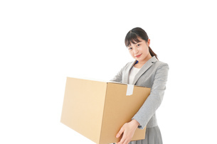 荷物を運ぶ若いビジネスウーマンの写真素材 [FYI04720513]
