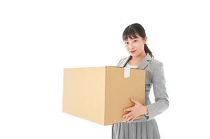 荷物を運ぶ若いビジネスウーマンの写真素材 [FYI04720514]