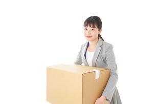 荷物を運ぶ若いビジネスウーマンの写真素材 [FYI04720515]