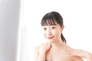 肌にクリームを塗る若い女性の写真素材 [FYI04720575]