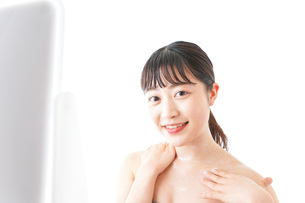 肌にクリームを塗る若い女性の写真素材 [FYI04720578]