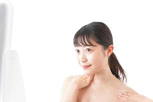 肌にクリームを塗る若い女性の写真素材 [FYI04720580]