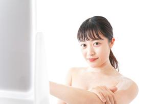 肌にクリームを塗る若い女性の写真素材 [FYI04720583]