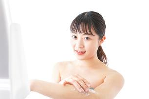 肌にクリームを塗る若い女性の写真素材 [FYI04720587]