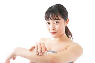 肌にクリームを塗る若い女性の写真素材 [FYI04720606]