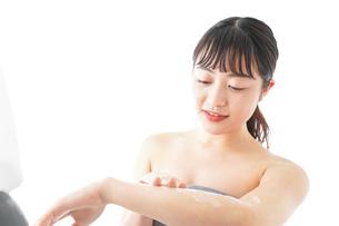 肌にクリームを塗る若い女性の写真素材 [FYI04720610]