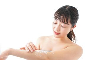 肌にクリームを塗る若い女性の写真素材 [FYI04720616]