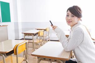 教室で携帯電話を使う学生の写真素材 [FYI04721215]