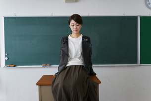 教壇に座る不良学生の写真素材 [FYI04721299]