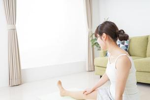 部屋でストレッチをする女性の写真素材 [FYI04722032]