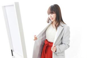 服を試着する女性の写真素材 [FYI04722124]
