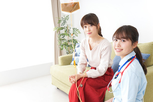 在宅で治療を受ける患者と訪問ナースの写真素材 [FYI04722323]