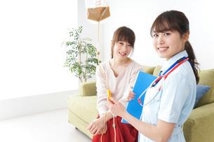 在宅で治療を受ける患者と訪問ナースの写真素材 [FYI04722327]