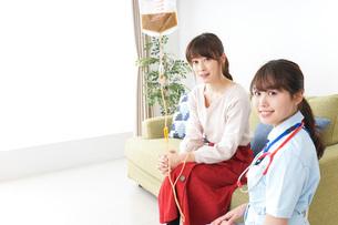 在宅で治療を受ける患者と訪問ナースの写真素材 [FYI04722332]