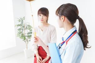 病院で診察を受ける患者とナースの写真素材 [FYI04722368]