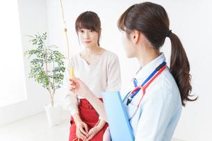 病院で診察を受ける患者とナースの写真素材 [FYI04722370]