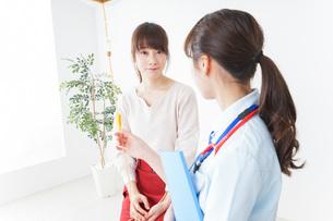 病院で診察を受ける患者とナースの写真素材 [FYI04722371]