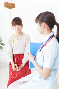 病院で診察を受ける患者とナースの写真素材 [FYI04722372]