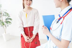 病院で診察を受ける患者とナースの写真素材 [FYI04722376]