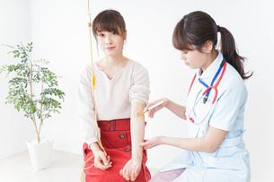 病院で診察を受ける患者とナースの写真素材 [FYI04722383]