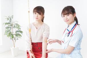 病院で診察を受ける患者とナースの写真素材 [FYI04722384]
