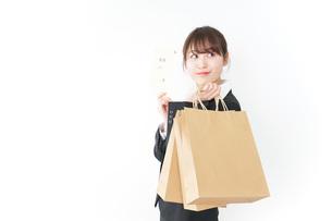 給料でショッピングをするビジネスウーマンの写真素材 [FYI04723150]