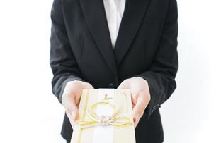 祝儀袋を渡すスーツ姿の女性の写真素材 [FYI04723320]