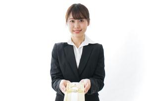 祝儀袋を渡すスーツ姿の女性の写真素材 [FYI04723322]