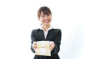 祝儀袋を渡すスーツ姿の女性の写真素材 [FYI04723335]