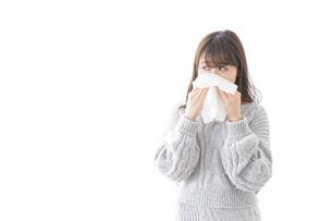 風邪・花粉症で鼻をかむ女性の写真素材 [FYI04723486]