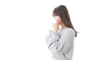 風邪・花粉症で鼻をかむ女性の写真素材 [FYI04723487]