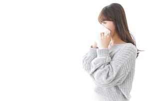 風邪・花粉症で鼻をかむ女性の写真素材 [FYI04723488]