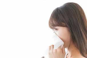 風邪・花粉症で鼻をかむ女性の写真素材 [FYI04723493]