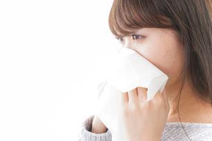 風邪・花粉症で鼻をかむ女性の写真素材 [FYI04723496]
