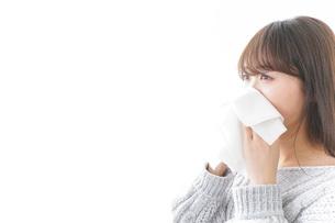 風邪・花粉症で鼻をかむ女性の写真素材 [FYI04723498]