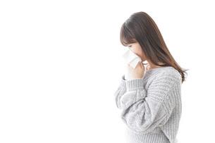 風邪・花粉症で鼻をかむ女性の写真素材 [FYI04723502]