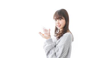 錠剤・サプリメントを飲む女性の写真素材 [FYI04723507]