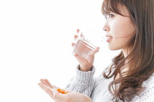 錠剤・サプリメントを飲む女性の写真素材 [FYI04723515]