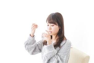 粉薬を服用する女性の写真素材 [FYI04723552]