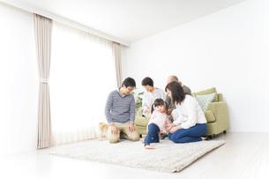 犬の世話をする3世代家族の写真素材 [FYI04723612]
