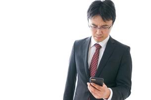 スマホを使うビジネスマンの写真素材 [FYI04724247]