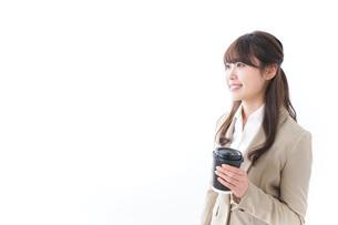 コンビニでコーヒーを買うビジネスウーマンの写真素材 [FYI04724534]