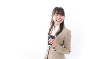 コンビニでコーヒーを買うビジネスウーマンの写真素材 [FYI04724535]