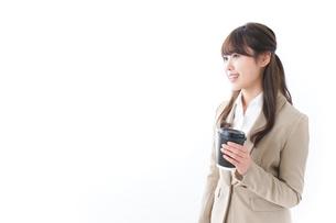 コンビニでコーヒーを買うビジネスウーマンの写真素材 [FYI04724537]