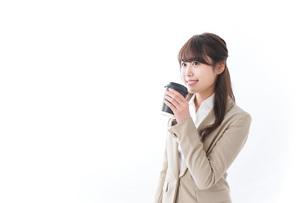 コンビニでコーヒーを買うビジネスウーマンの写真素材 [FYI04724551]