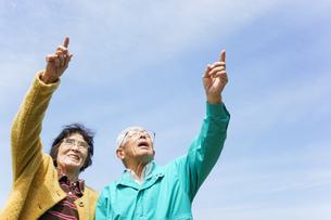 空を指差す高齢夫婦の写真素材 [FYI04724732]