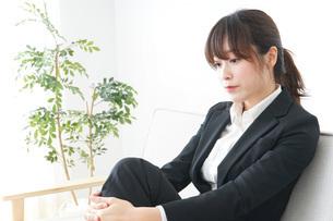 スーツでオフィスに座るビジネスウーマンの写真素材 [FYI04724943]