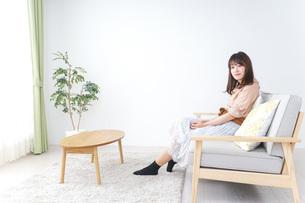 部屋でリラックスをする若い女性の写真素材 [FYI04724997]